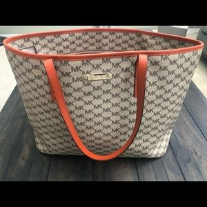Michael Kors Emry tote with orange accent.